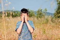Boy playing hide and seek in field