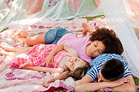 Three friends sleeping in summer netting tent