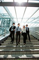 Four businesspeople on steps