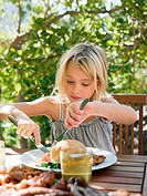 Girl eating meal, outdoors