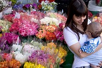 Woman beside flowers holding a baby, Toronto, Ontario