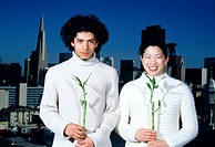Young couple holding bamboo plants in front of the San Francisco city skyline