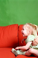 Little girl sitting on a sofa laughing