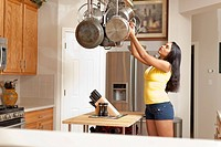 Mixed race woman reaching for pan in kitchen
