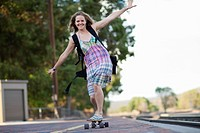Caucasian woman riding skateboard