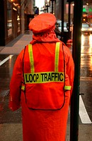 Rear view of a traffic personnel standing on the sidewalk
