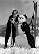 sports, winter sports, skiing, woman with poodle and ski standing beside snowman, 1950s,
