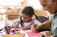 Grandfather and granddaughter drawing together