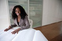 Black businesswoman looking at blueprints