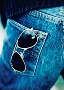 Sunglasses sticking in a trouser pocket