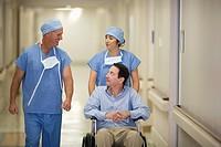 Doctors pushing patient in wheelchair in hospital corridor