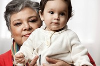 Hispanic grandmother sitting with granddaughter