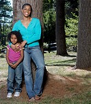African American mother hugging daughter in park