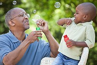 Black grandfather and grandson blowing bubbles