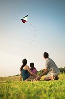 Family watching kite in sky