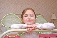 Girl Wearing Wings Sitting on Bed