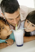 Father Sharing Glass of Milk with Daughters