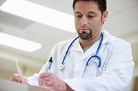 Physician Filling Out Paperwork
