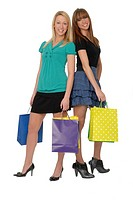 Two woman friends in their early 20s, holding shopping bags, smiling and looking at viewer