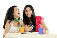 Two friends looking at a mobile phone and laughing