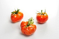 Horizontal image of three tomatoes on white background