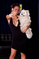 Widow woman in sexy black dress hold white dog and pointin wiht