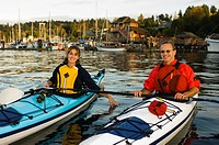 kayakers paddle in front of village, Cowichan Bay, Vancouver Island, British Columbia, Canada.