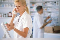 Pharmacist on Phone Holding Bottle of Pills
