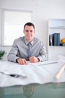 Close up of smiling architect sitting behind a table working on a construction plan