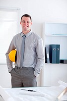 Architect standing in his office and carrying a helm