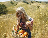 Young woman eating orange in meadow, close_up, portrait