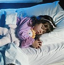 Girl sleeping on bed with doll