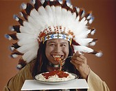 Tribal man with feathered headdress eating spaghetti, smiling, portrait