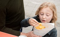 Two little girls eating french fries in a traditional Belgian fritkot