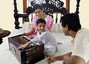 Boy playing on a harmonium