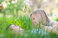 Smiling couple laying in grass (thumbnail)