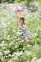 Girl playing with pinwheel in field of flowers