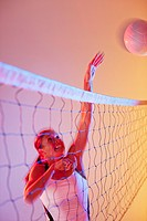Volleyball player spiking ball over net