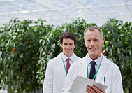 Scientist using clipboard in greenhouse