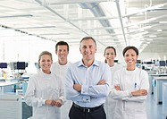 Scientists and businessman smiling in lab
