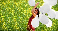 Young woman with balloons in a field