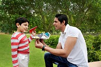 Father and son having fun with paper airplanes