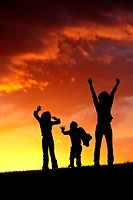 A woman and her two kids jump for joy at sunset