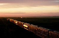A freight train rolls under a twilight sky, paralleling Interstate 70 in eastern Colorado.