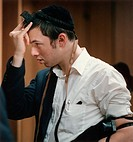 A student at an Orthodox Jewish yeshiva in Philadelphia adjusts his tfillin so that it sits on his forehead between his eyes.