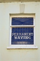 The first floor window of a former beauty salon advertises Permanent Waving services.