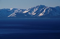The snowy Sierra Nevada Mountains line the south shore of Lake Tahoe.