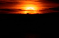 The moon partially blocks the sun as they set behind dark clouds. This eclipse is annular, meaning that a ring of light from the sun surrounds the moo...