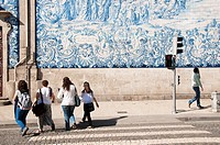 people crossing the street close to Igrecia do Carmo church covered with azulejos, Igrecia do Carmo in Porto is a popular church built by the Carmelit...