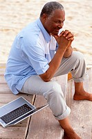 Man Sitting with Laptop on Dock